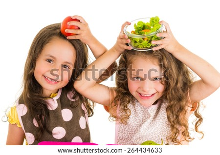 Beautiful healthy little girls holding fruits and vegetables on her heads isolated on white - stock photo