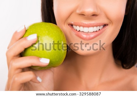 Beautiful healthy smile. Girl smiling with green apple - stock photo