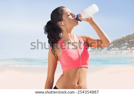 Beautiful healthy woman drinking water against beautiful beach and blue sky - stock photo