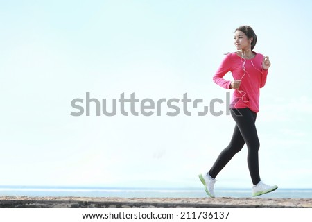Beautiful healthy woman in pink running on the beach - stock photo