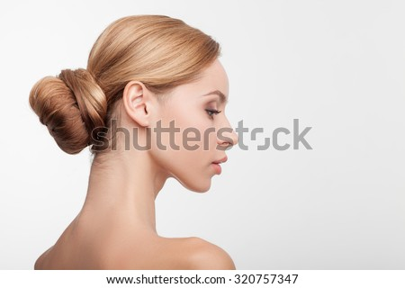 Beautiful healthy woman is standing in profile. She is looking forward confidently and relaxing. Her skin is smooth and perfect. Isolated and copy space in right side - stock photo