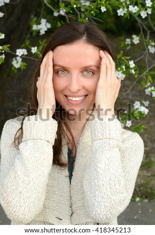 Beautiful healthy woman touching her skin, on a background of a blossoming tree - stock photo