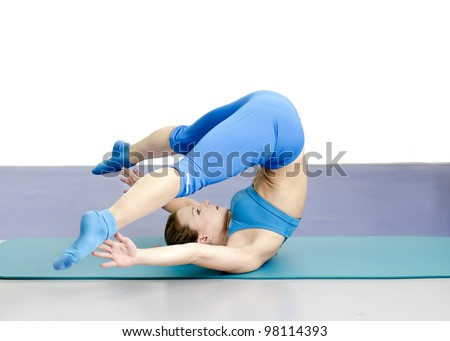Beautiful healthy young woman in the gym working out, making yoga exercise with legs spread in the air, laying on her back. - stock photo