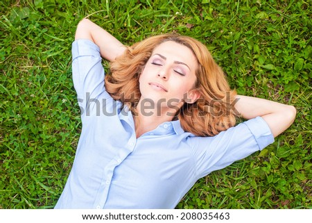 Beautiful healthy Young Woman lying and relaxing on the green grass,  - stock photo
