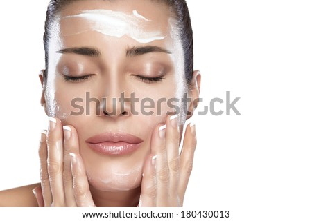 Beautiful healthy young woman with eyes closed while applying moisturizer to her clean face using gentle soft touches, close-up portrait isolated on white. Perfect skin. Skincare concept. Spa woman - stock photo