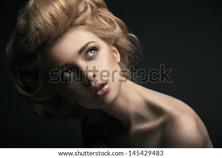Beautiful high fashion female model with abstract hair style behind the table - stock photo
