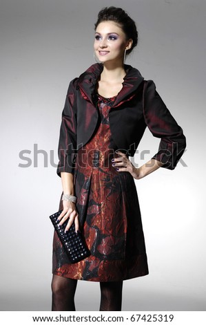Beautiful high fashion model in modern clothes hold purse posing in light background - stock photo