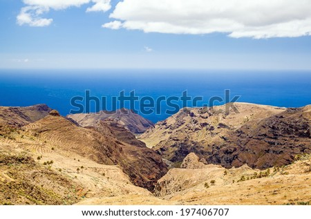 Beautiful hiking mountains landscape yellow meadow, blue sky clouds and ocean, Canary Islands La Gomera, Spain - stock photo