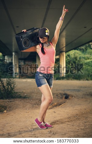 Beautiful hip hop woman with a cap which holding a tape recorder on shoulder listening to music and has raised arm. Toned image. - stock photo