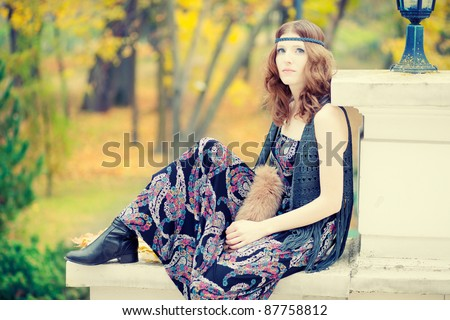 Beautiful hippie girl sitting in autumn scenery wearing maxi long dress and gorgeous make up. - stock photo