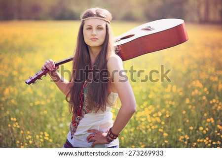 Beautiful hippie woman with guitar in a summer field. Peace and harmony - stock photo