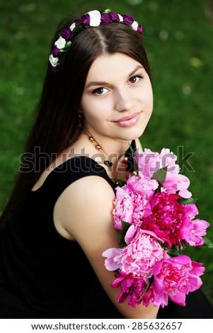 Beautiful hippy bohemian fashion style model in beautiful lake environment. Brunette woman with flowers enjoying nature against nature background - stock photo