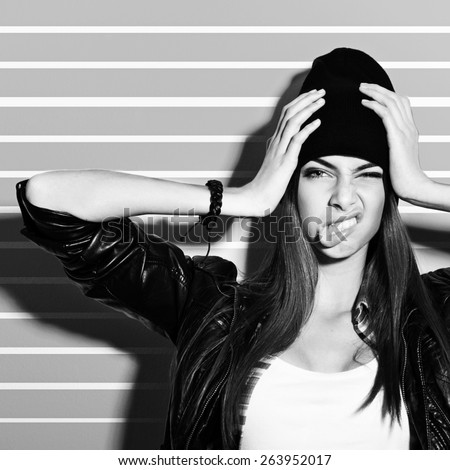 Beautiful hipster Caucasian brunette teenage girl with black beanie hat and black leather jacket posing making funny facial expression. Medium retouch, black and white, square format. - stock photo