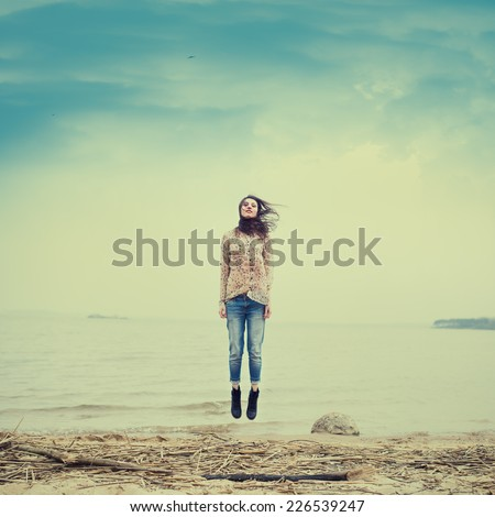 beautiful hipster girl flying on the beach - stock photo