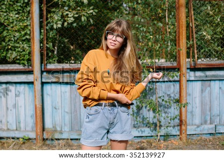 Beautiful hipster girl posing  in the park - stock photo