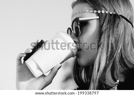 Beautiful hipster woman in sunglasses with cup of coffee. Close-up black and white  lifestyle outdoor portrait - stock photo