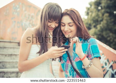 beautiful hipster young women sisters friends using smartphone  in the city - stock photo