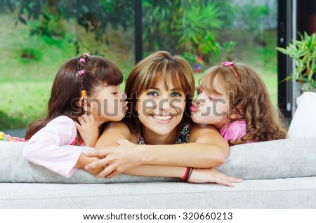 Beautiful hispanic family of four posing with heads sticking up from back of sofa looking at camera smiling. - stock photo