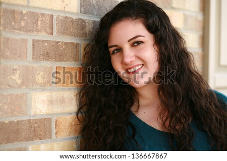 beautiful hispanic girl with long curly hair smiling - stock photo