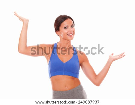 Beautiful hispanic lady in sportswear putting hands up while looking at you against white background - copyspace - stock photo