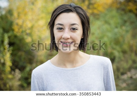 Beautiful Hispanic teen girl outdoor portrait. Cute and smiling with a mouth full of braces - stock photo