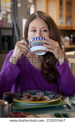 Beautiful Hispanic woman in deep thoughts eating breakfast - stock photo