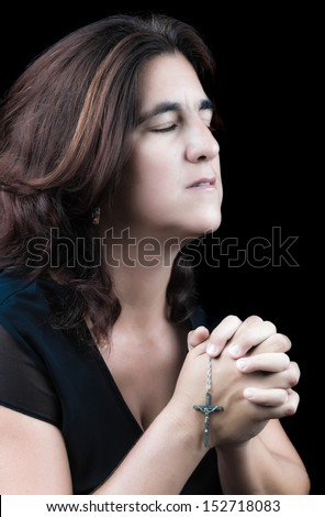 Beautiful hispanic woman praying with her eyes closed and holding a small crucifix (side view, isolated on black) - stock photo