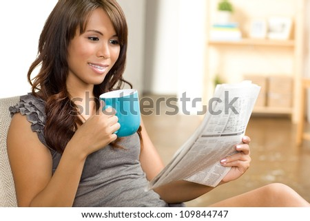 Beautiful Hispanic woman relaxing at home wearing short sleeve gray shirt and shorts. - stock photo