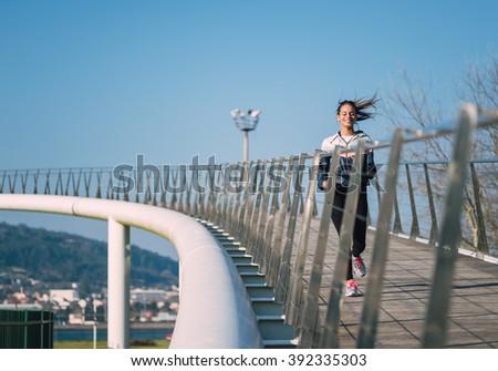 Beautiful hispanic woman running on a bridge outdoors - stock photo