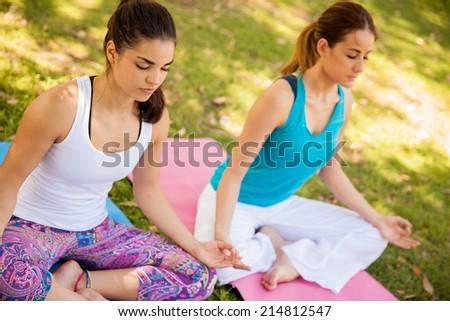 Beautiful Hispanic women meditating and doing yoga outdoors - stock photo