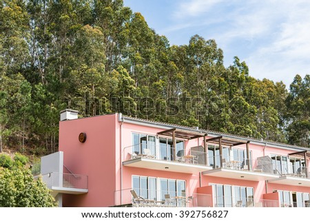 Beautiful holiday resort with hill behind it in Madeira.  Scenic view of beautiful tan colored building or resort hotel with tall grassy hill behind it in Madeira Portugal - stock photo