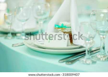Beautiful holiday table setting in white and blue color with a gift on the plate - stock photo