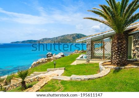 Beautiful holiday villa house on coast of Sardinia island - view from promenade at Campolungo beach, Italy - stock photo