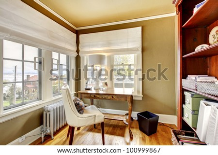 Beautiful home office with green walls and white chair. - stock photo