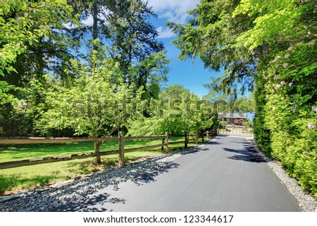 Beautiful home with private gates, long driveway and garden. - stock photo