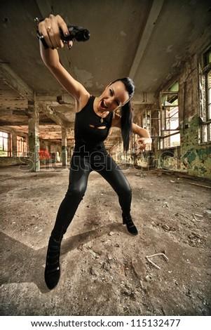 beautiful hooligan pointing with a gun - stock photo