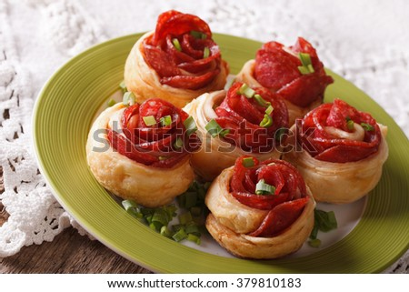 Beautiful hot sandwiches with salami in the form of a flower on a plate on the table. horizontal