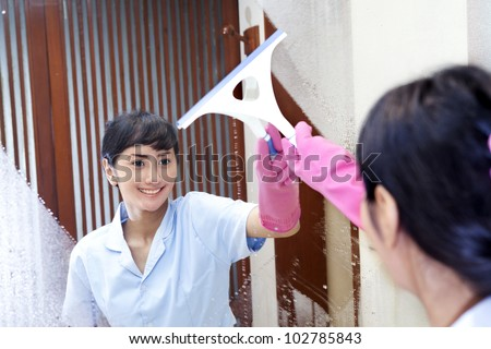 Beautiful Hotel maid wearing pink gloves cleaning up the bathroom - stock photo