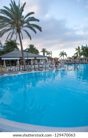 Beautiful hotel swimming pool before sunrise in the morning - stock photo