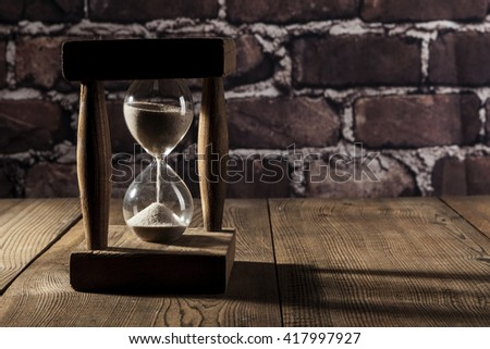 Beautiful hourglass on brown wood table with shadow - stock photo