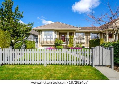 Beautiful house against blue sky with clouds on a sunny day in Vancouver, Canada. - stock photo