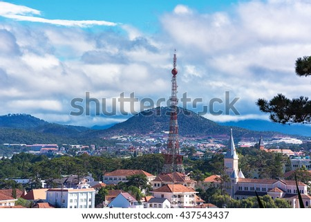 Beautiful houses with tile roofs and Da Lat Eiffel Tower in the Da Lat city (Dalat) on the blue sky background in Vietnam. Dalat is known as one of the most popular tourist destinations of Vietnam. - stock photo