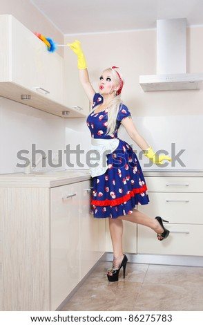 Beautiful housewife is cleaning the kitchen - stock photo