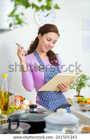 beautiful housewife preparing dinner in the kitchen with a prescription - stock photo