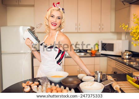 Beautiful housewife whisking eggs with a mixer - stock photo