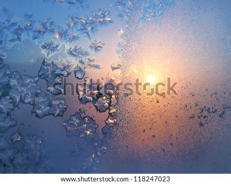 Beautiful ice pattern and sunlight on winter glass - stock photo