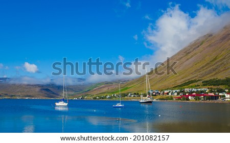 Beautiful Icelandic Vibrant Summer Landscape with Fjord, Isafjordur, Vestfirdir, with boat. - stock photo