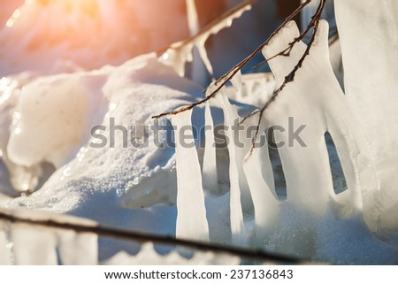 Beautiful icicles at sunset. Winter landscape with ice on the lake. Small depth of sharpness - stock photo