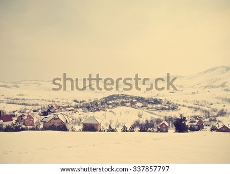 Beautiful, idyllic snowy winter landscape in mountains, on a foggy morning, with snow-covered rooftops of a small picturesque village. Image filtered in soft, faded, retro, vintage Instagram style. - stock photo