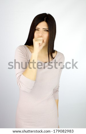 Beautiful ill woman coughing strong with hand in front of mouth - stock photo